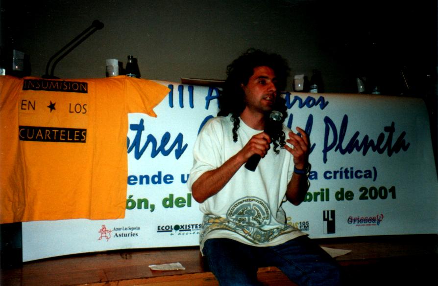 Foto que representa al que escribe este texto con un micrófono en la mano sentado  delante de una mesa y supuestamente ante un público que no se ve.