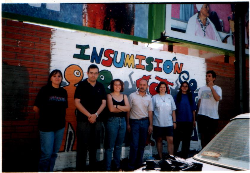 Pintada en una pared sobre «insumisión». Se ve a varias personas posando ante la pintada.
