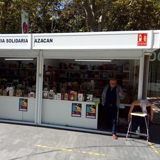 Foto del puesto de la ONG Azacán en la Feria del Libro Antiguo y de Ocasión, en la que se ven libros y a un señor saliendo del puesto.