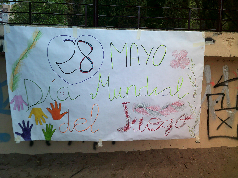 âncarta que dice 28 mayo Día Mundial del Juego con flores y manos de colores